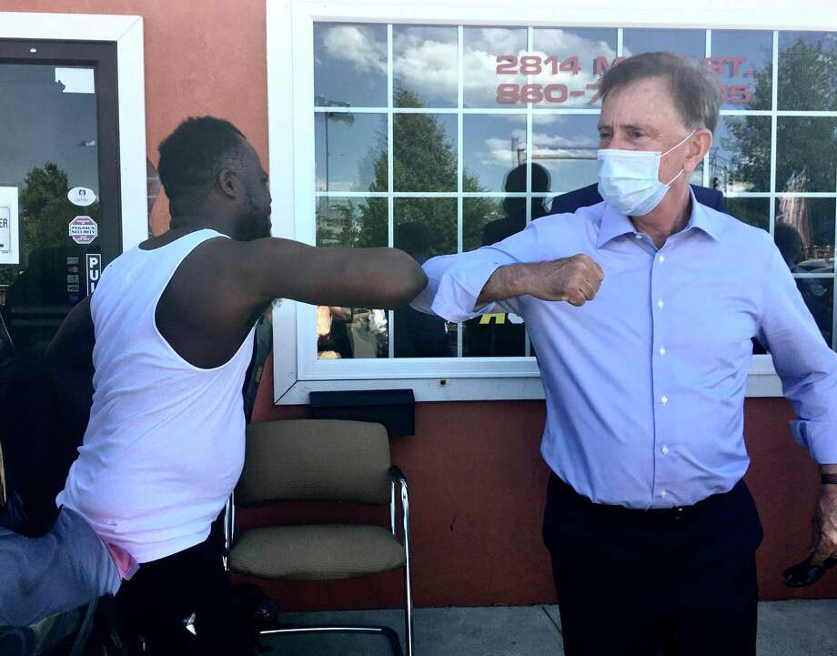 Gov. Ned Lamont took a walk in Hartford's North End Friday to talk with small business owners about the coronavirus crisis. He's pictured bumping elbows with Kenston Harry, owner of The Action Audio Store. Photo: Dan Haar / Hearst Connecticut Media