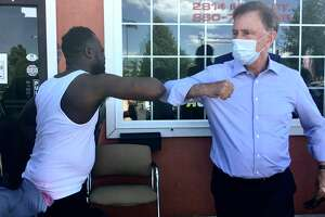 Gov. Ned Lamont took a walk in Hartford's North End Friday to talk with small business owners about the coronavirus crisis. He's pictured bumping elbows with Kenston Harry, owner of The Action Audio Store.