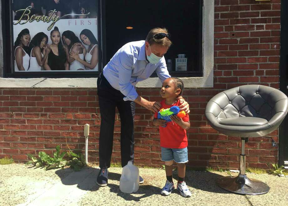 Gov. Ned Lamont took a walk in Hartford's North End Friday to talk with small business owners about the coronavirus crisis.  He's pictured with Destiny Hunter, owner of Beauty First, a maker of extensions and wigs, and with her 2-year-old son Jaquan Lindsey. Photo: Dan Haar/Hearst Connecticut Media