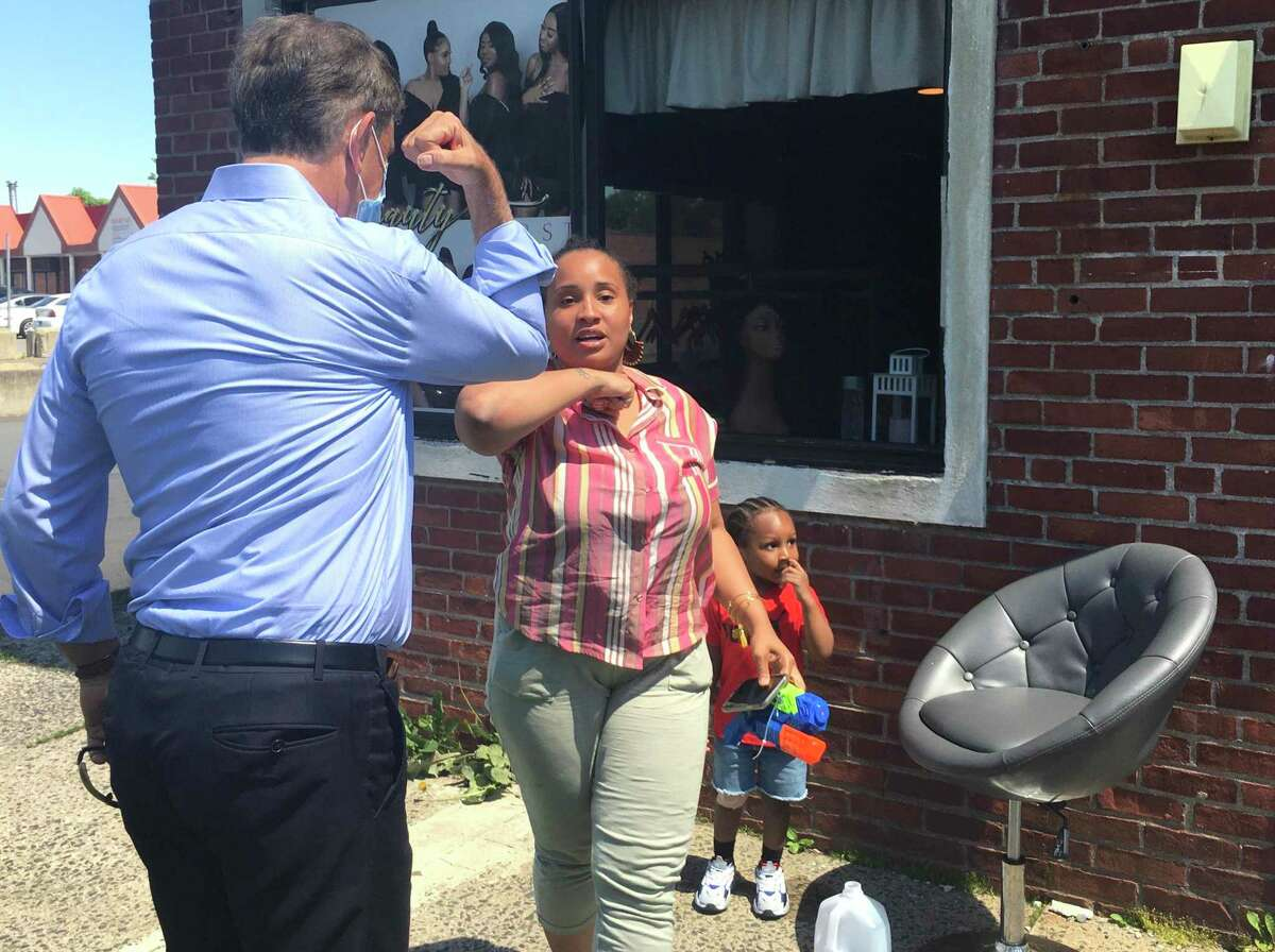 Gov. Ned Lamont took a walk in Hartford's North End Friday to talk with small business owners about the coronavirus crisis. He's pictured with Destiny Hunter, owner of Beauty First, a maker of extensions and wigs, and with her 2-year-old son Jaquan Lindsey.