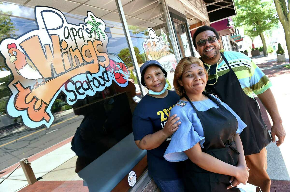 From left, Ernestine Green, her daughter, Brittany, and husband, James, are photographed at their newly opened takeout restaurant, Papa's Wings & Seafood, on Main Street in East Haven on June 12, 2020.