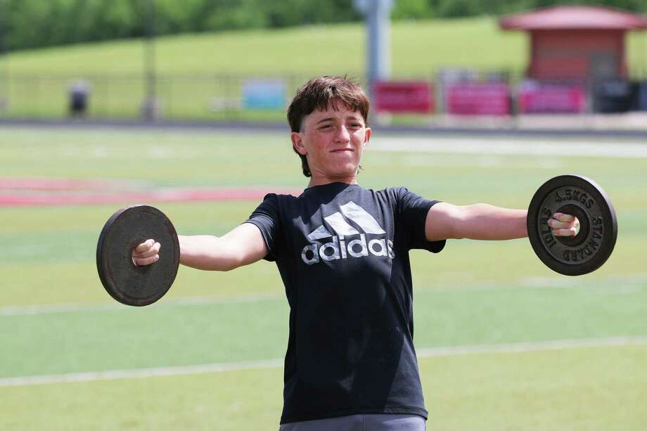 Ryder Miller holds 10- pound weights at arms-length to develop his forearms and biceps during F.A.T. Camp at Falcon Stadium in Huffman. Photo: David Taylor / Staff Photographer