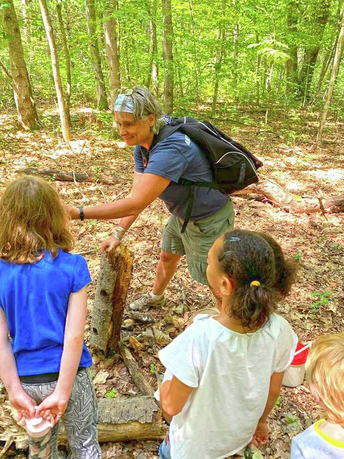 Summer camps in the area are still on, with new rules and new formats. At the Institute of American Indian Studies in Washington, assistant director Susan Sherf leads children in an activity at the 2019 camp. Photo: Contributed Photo /