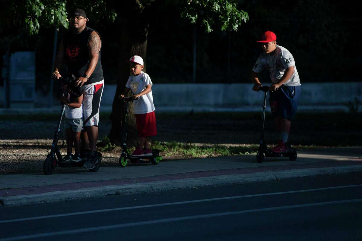 A family rides scooters along South Alamo Street. Hospitalizations for COVID-19 have reached an all-time high in Bexar County, about two weeks after the Memorial Day holiday, when more people ventured out of their homes.