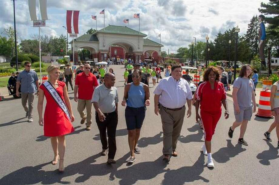 Gov. JB Pritzker joins 2019 State Fair Grand Marshal and East St. Louis native Jacki Joyner-Kersee and others for the grand opening of the 2019 Illinois State Fair in Springfield. The state announced Friday that the governor would cancel this year's Fairs in Springfield and Du Quoin by executive order because of the COVID-19 pandemic. Photo: Jerry Nowicki | Capitol News Illinois
