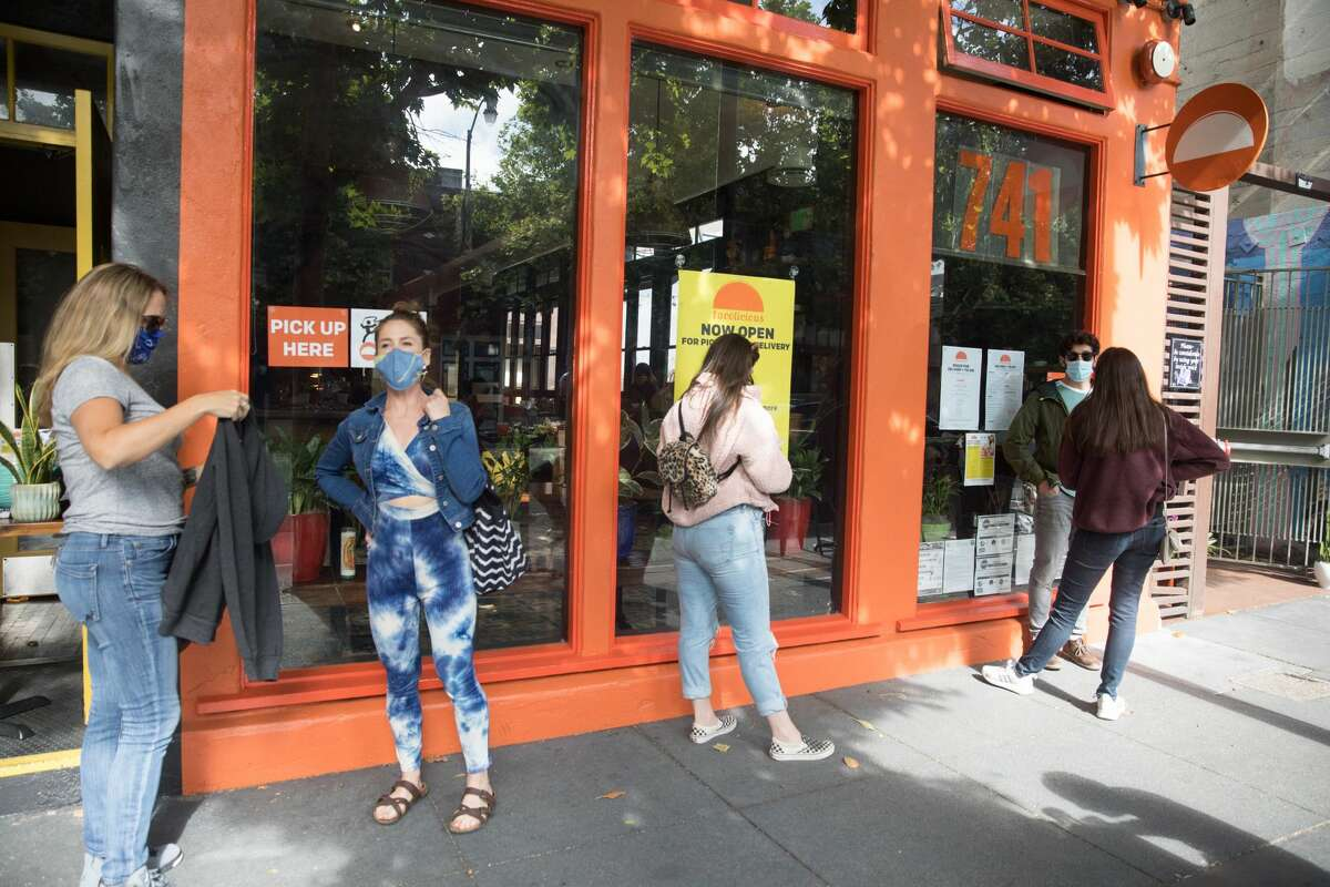 Customers wait in socially distanced lines for food at Tacolicious on Valencia Street in San Francisco on June 12, 2020.