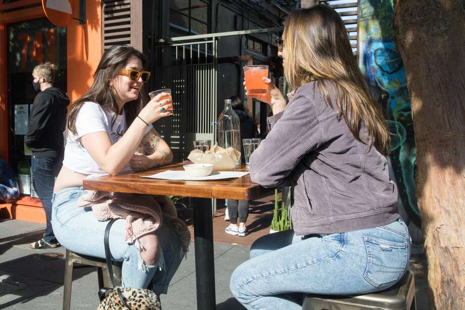 Haylie Aitken (left) and Rachel Pratley enjoy a margarita at Tacolicious on Valencia Street in San Francisco. The restaurant started offering outdoor food service on June 12, 2020. Photo: Douglas Zimmerman/SFGATE / SFGATE