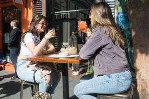 (Left to right) Haylie Aitken and Rachel Pratley enjoy a margarita atTacolicious on Valencia Street in San Francisco, Calif.. The restaurant started offering outdoor food service on June 12, 2020.