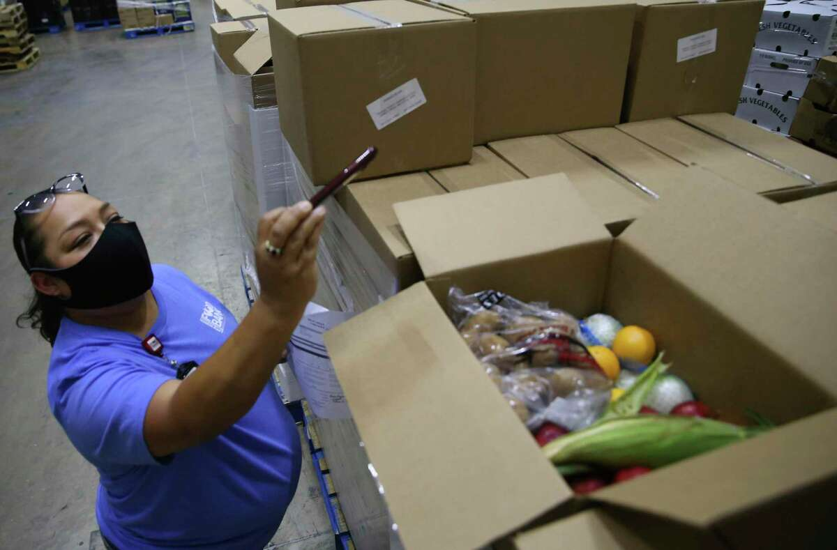 Dayna Robokowski, San Antonio Food Bank produce procurement manager, documents the first boxes of produce delivered by Avila Produce for CRE8AD8 as part of CRE8AD8's $39 million USDA contract to help provide food relief on Thursday, May 28, 2020.