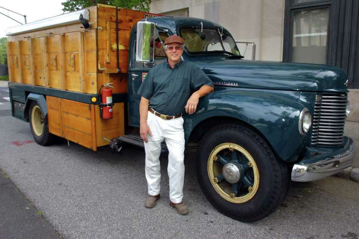 Douglas Coffin of Big Green Truck Pizza stands in front of one of his antique International Harvester KB-5 trucks, which has restored and refitted into a mobile wood fired pizza oven.