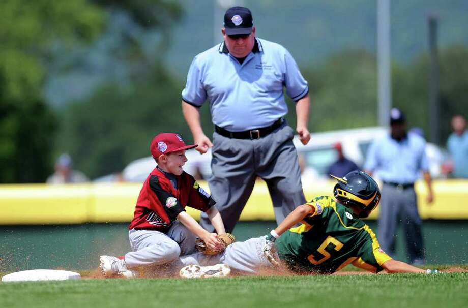 An umpire watches as Nate Klein tags Northwest runner Ryan Lacey at third base during Fairfield American's first game of the Little League World Series in Williamsport, Penn., on Friday, August 20, 2010. Photo: Lindsay Niegelberg / Connecticut Post