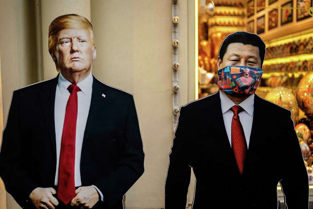 Cardboard figures of Chinese President Xi Jinping wearing a face mask and U.S. President Donald Trump stand in front of a souvenir shop in downtown Moscow on June 3