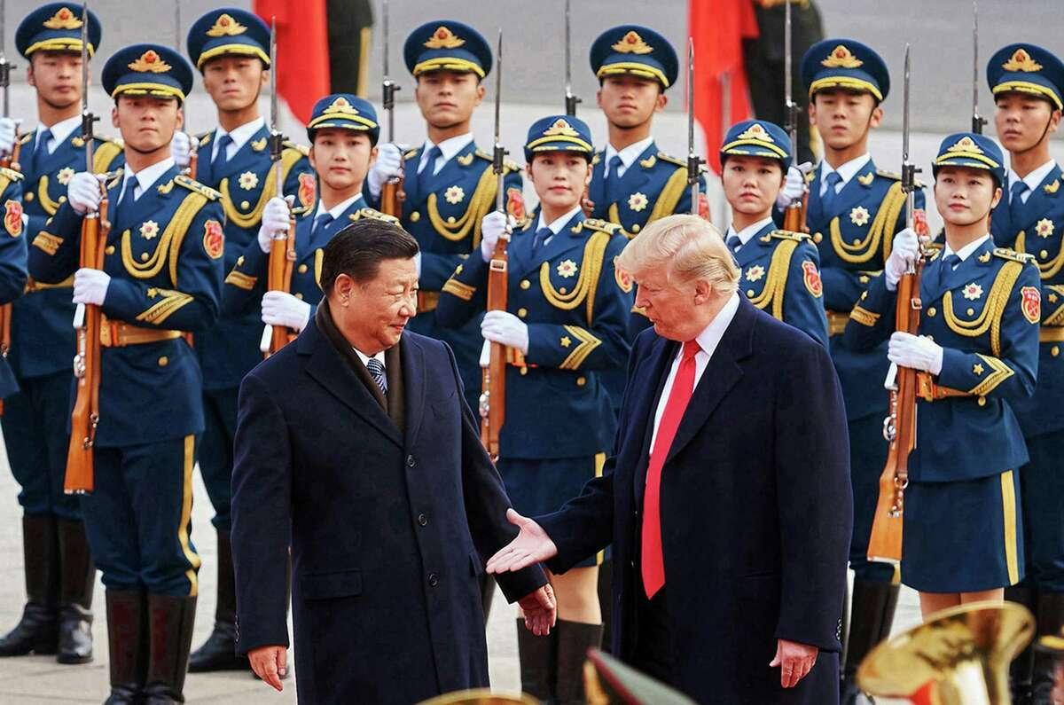 From left, Chinese President Xi Jinping and U.S. President Donald Trump shake hands on Nov. 9, 2017, during a meeting outside the Great Hall of the People in Beijing.