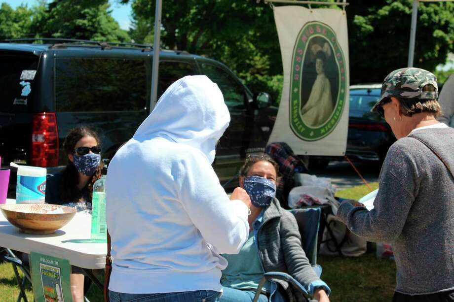 Volunteers at the entrance to the Frankfort Farmers Market offer hand sanitizer and masks to visitors. (Photo/Colin Merry)