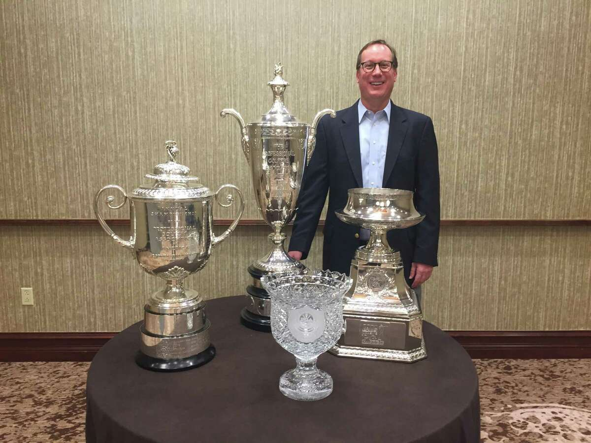 Former Greater Hartford Open tournament director Dan Baker, now with the PGA of America, poses with, left to right, the PGA Championship trophy, the Senior PGA Championship, the PGA Professional Championship crystal and the KPMG Women's PGA Championship.