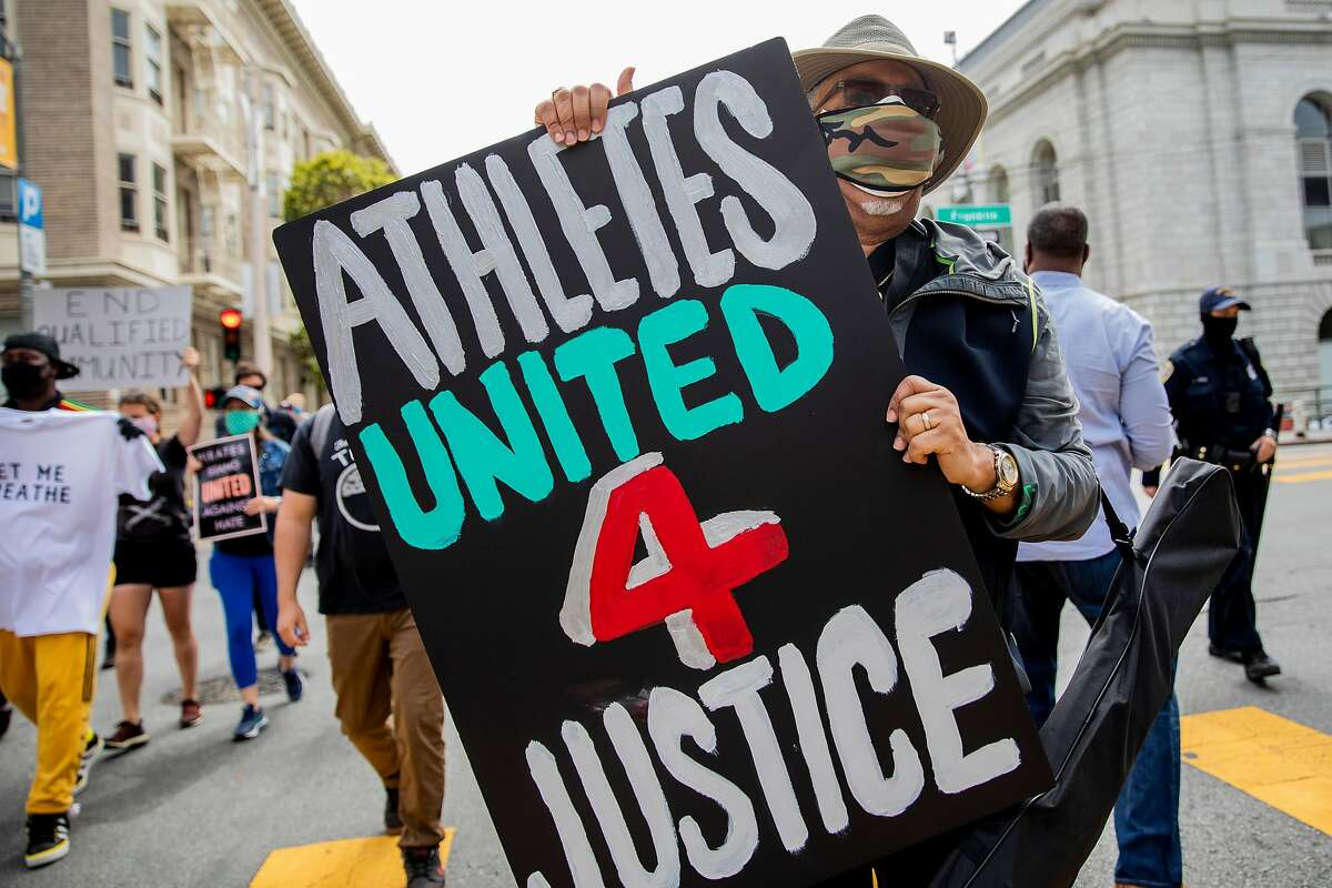 Derek Toliver, who represented San Francisco in the 1967 high-jump and jr. olympics, carries a sign while joining other former Bay Area athletes march down McAllister Street in San Francisco, Calif. Friday, June 12, 2020 during an Athletes United for Justice rally organized by Midnight Basketball League�s Lawrence Gray.