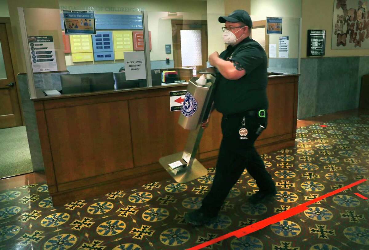Chad Sies of Facility Management, carries a hand sanitation unit to be placed in front of a courtroom on the third floor of the historic Bexar County Courthouse to make the area COVID-19 compliant as courtrooms begin re-opening next week, on Thursday, June, 11, 2020.