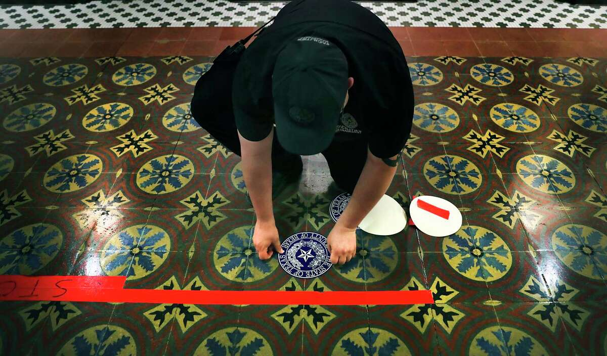 Chad Sies of Facility Management, places distancing markers on the floor on the third floor of the historic Bexar County Courthouse to make the area COVID-19 compliant as courtrooms begin re-opening next week, on Thursday, June, 11, 2020.