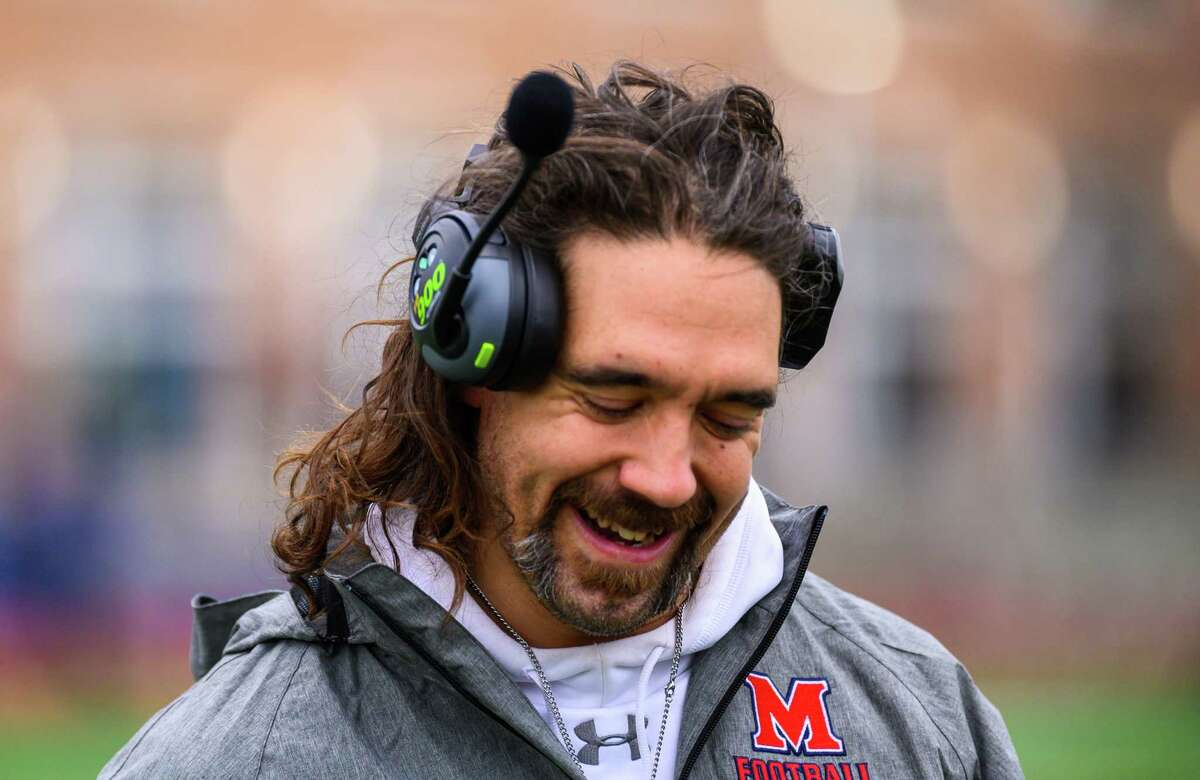 McMahon football coach Jeff Queiroga, shown during a game against Norwalk on Nov. 28, donates his hair to a charity that makes wigs for pediatric cancer patients. During the COVID-19 pandemic, Queiroga and fellow McMahon teacher Nick Banas started a program that provided nearly 2,000 meals to Norwalk residents.