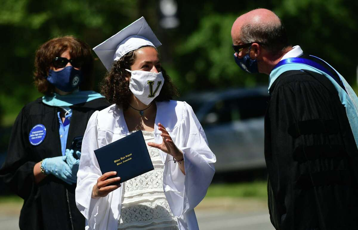 Graduates including Kailey Titus arrive by motorcade at the Wilton High School commencement ceremoniy Saturday, June 13, 2020, in Wilton, Conn.