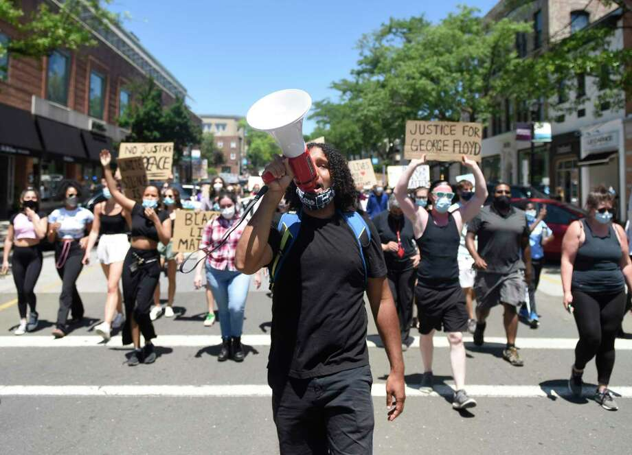 Norwalk's Elijah Manning leads the Black Lives Matter Wake Up March from Town Hall to the Public Safety Complex in Greenwich, Conn. Saturday, June 13, 2020. Organized by the group Burst Their Bubble, the peaceful protest featured more than 200 participants marching through the streets to confront racism and police brutality in local communities and throughout the country. The event featured several speakers outside the police station and ended with participants taking a knee for eight minutes and 46 seconds in honor of George Floyd. Photo: Tyler Sizemore / Hearst Connecticut Media / Greenwich Time