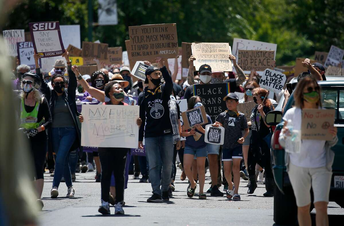 Demonstrators march on College Avenue from the Rockridge BART station in Oakland to Sproul Plaza at UC Berkeley on Saturday, June 13, 2020 to protest for racial justice and against excessive police force.