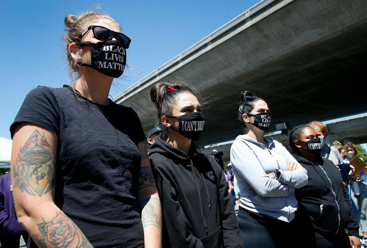 From left, Courtney De Soto, Renee Ruiz-Pacheco, Anastasia Ruiz and Amaya Leta-Pombo listen to speeches before a march begins from the Rockridge BART station in Oakland to Sproul Plaza at UC Berkeley on Saturday, June 13, 2020 to protest for racial justice and against excessive police force.