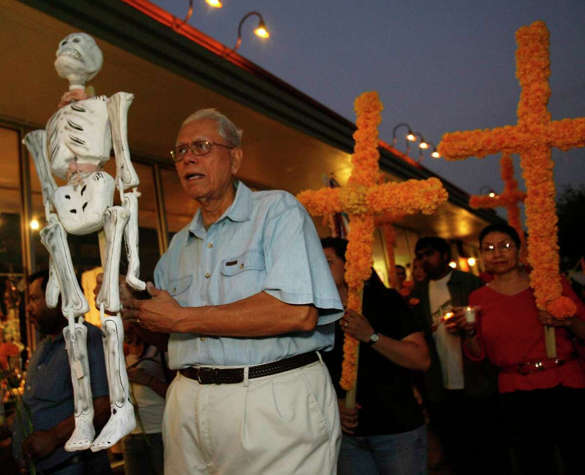 Macario Ramirez carries a skeleton up the street during a Day of the Dead procession that started on 19th street in the Heights and ended at Casa Ramirez, his store, in 2008.