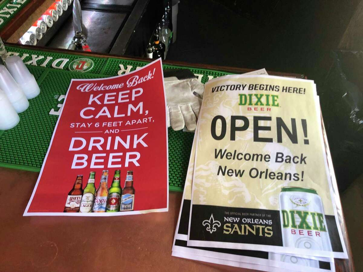 In this Friday, June 12, 2020 photo, stacks of signs for welcoming back patrons sit on the bar at Lafitte's Blacksmith Shop Bar on Bourbon Street in New Orleans. The city is allowing bars to open a€?