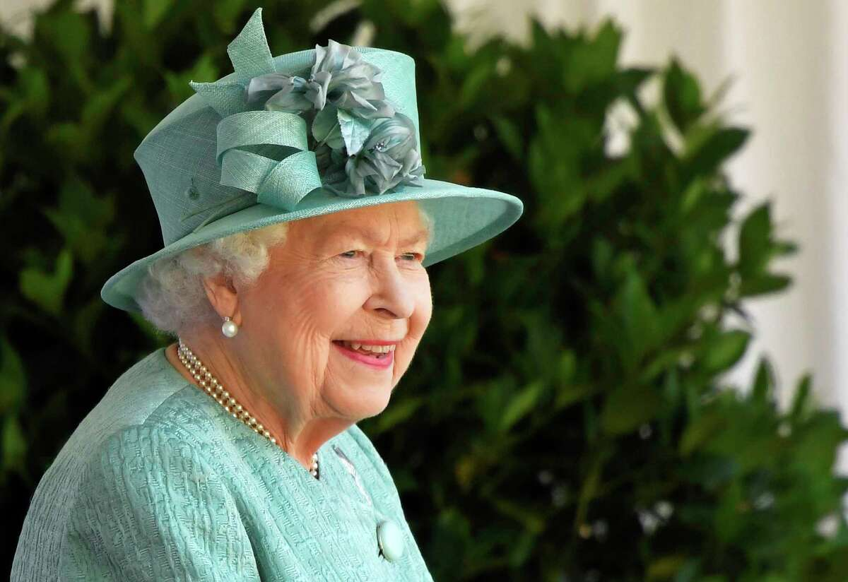 Britain's Queen Elizabeth II reacts as she looks out during a ceremony to mark her official birthday at Windsor Castle in Windsor, England, Saturday June 13, 2020. Queen Elizabeth IIa€™s birthday is being marked with a smaller ceremony than usual this year, as the annual Trooping the Color parade is canceled amid the coronavirus pandemic. The Queen celebrates her 94th birthday this year. (Toby Melville/Pool via AP)