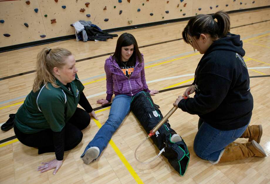 Midland College Head Athletic Trainer Sonya Mikeska watches while Andrews High School freshman Adaly Gardea, 15, removes air form a vacuum immobilizer to brace Odessa High sophomore Connie Craddock's, 15, leg Saturday at the Student Athletic Training Workshop. Area high school and junior high students are learning the basics of injury evaluation and how to stabilize injured players as well as the future of the athletic training profession. Cindeka Nealy/Reporter-Telegram Photo: Cindeka Nealy,  Reporter-Telegram