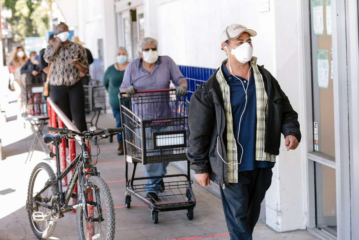 Shoppers wear masks as they wait in line to enter Cardenas Market in the Fruitvale District of Oakland, Calif, on Thursday, May 28, 2020. 12 employees of Cardenas Market on High Street recently tested positive for Covid-19 as Alameda County passed Santa Clara County as the hardest hit county in the Bay Area by the novel coronavirus as the East Bay community wrestled with a recent surge in cases that public health officials can't yet explain.