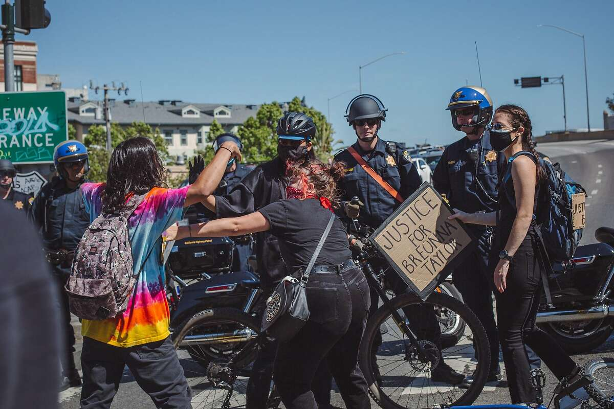 Organizers deescelate a confrontation between a protestor and SFPD at Market Street and Octavia Blvd in San Francisco on Saturday during a march in support of the Black Lives Matter movement.