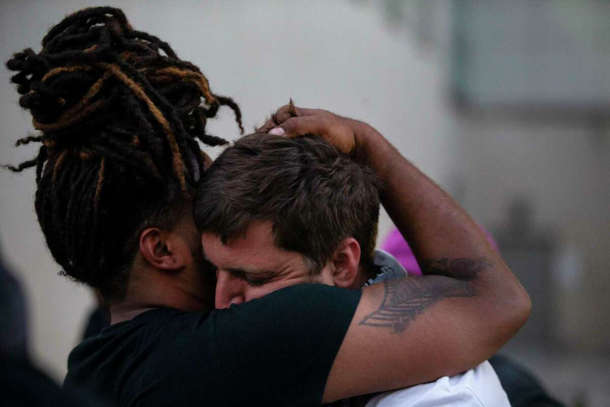 Antonio Lee embraces Brandon Mowles after Mowles was released from being detained on suspicion of vandalism outside Public Safety Headquarters in downtown San Antonio on June 3, 2020.