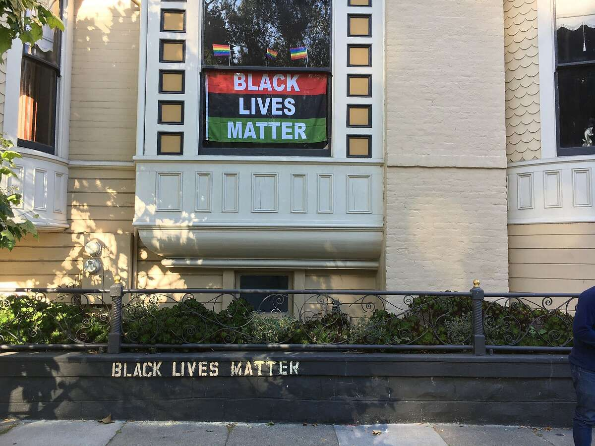 The words Black Lives Matter are stenciled on a retaining wall in and shown in the window of a house the Pacific Heights neighborhood of San Francisco, Calif., on Saturday, June 13, 2020.