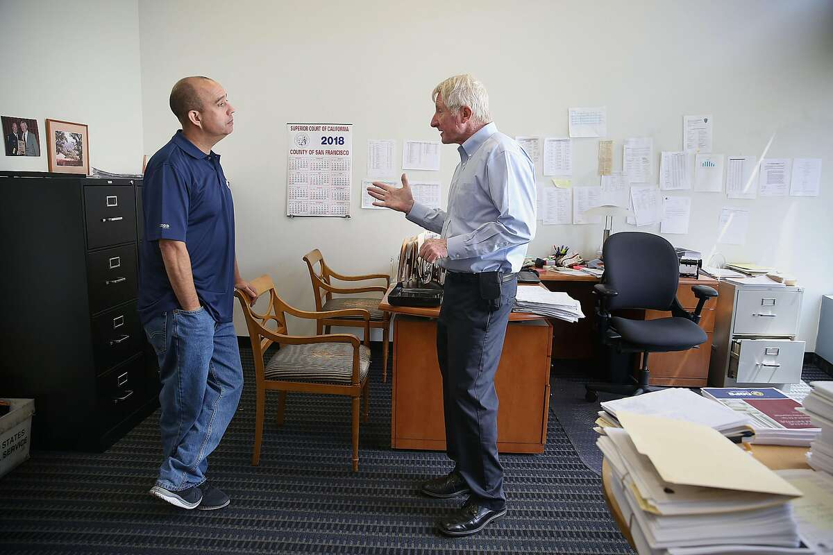 Tony Montoya (left), the new president of the San Francisco Police Officers Association, talks with legal defense administrator and retired captain Paul Chignell (right) as they talk at work on Thursday, May 31, 2018 in San Francisco, Calif.