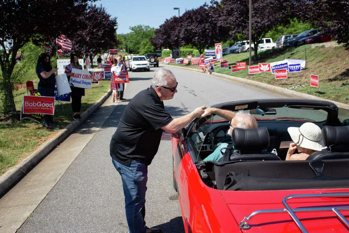 Rep. Denver Riggleman, R-Va., greets delegates at they arrive to cast votes at a drive-through convention at Tree of Life Ministries in Lynchburg, Va., on Saturday.