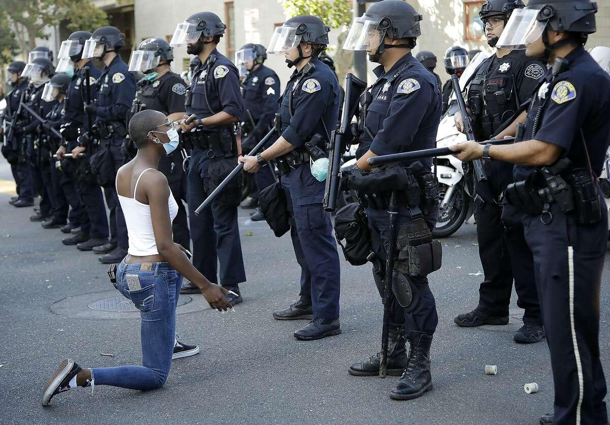 A masked protestor kneels before San Jose police on Friday, May 29, 2020, in San Jose, Calif. (AP Photo/Ben Margot)