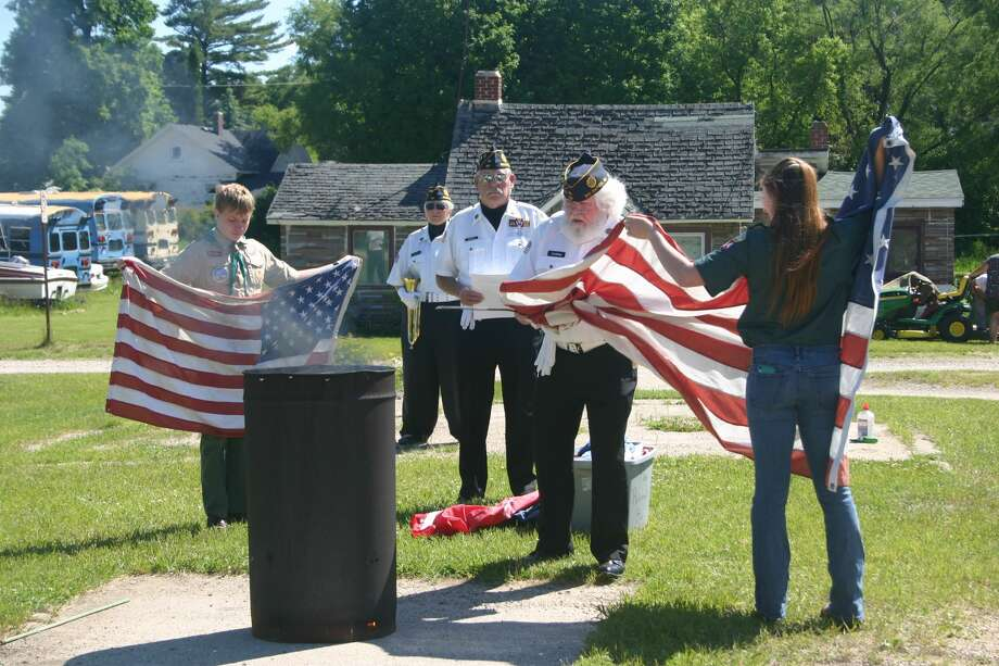 American Legion Post 98 in Big Rapids hosted a Flag Day ceremony June 14, during which they properly disposed of worn and tattered flags that were no longer serviceable. Veterans wee assisted by local scouts in the burning of the flags. Photo: Pioneer Photo/Cathie Crew