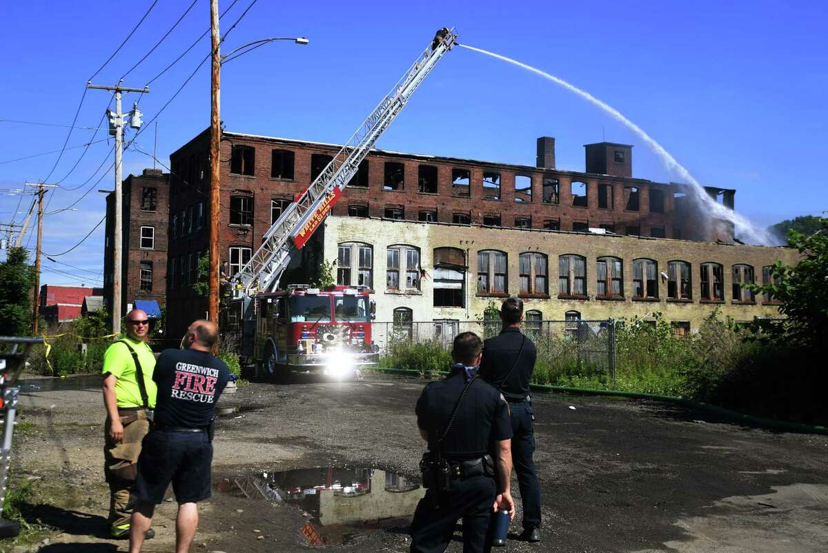 Firefighters continue to pour water on the smoldering remains of the Star Pin factory fire on Canal Street in Shelton on Sunday.