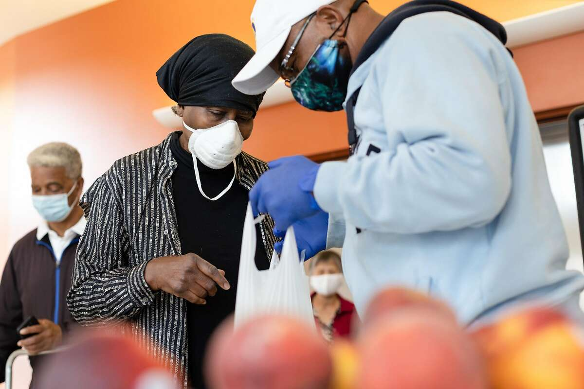Geoffrey Grier (right), a staff member with the Bayview Senior Services, packs a bag with fruit for Nettie Fabian at Dr. George W. Davis Senior Center on Friday, June 12, 2020, in San Francisco, Calif.