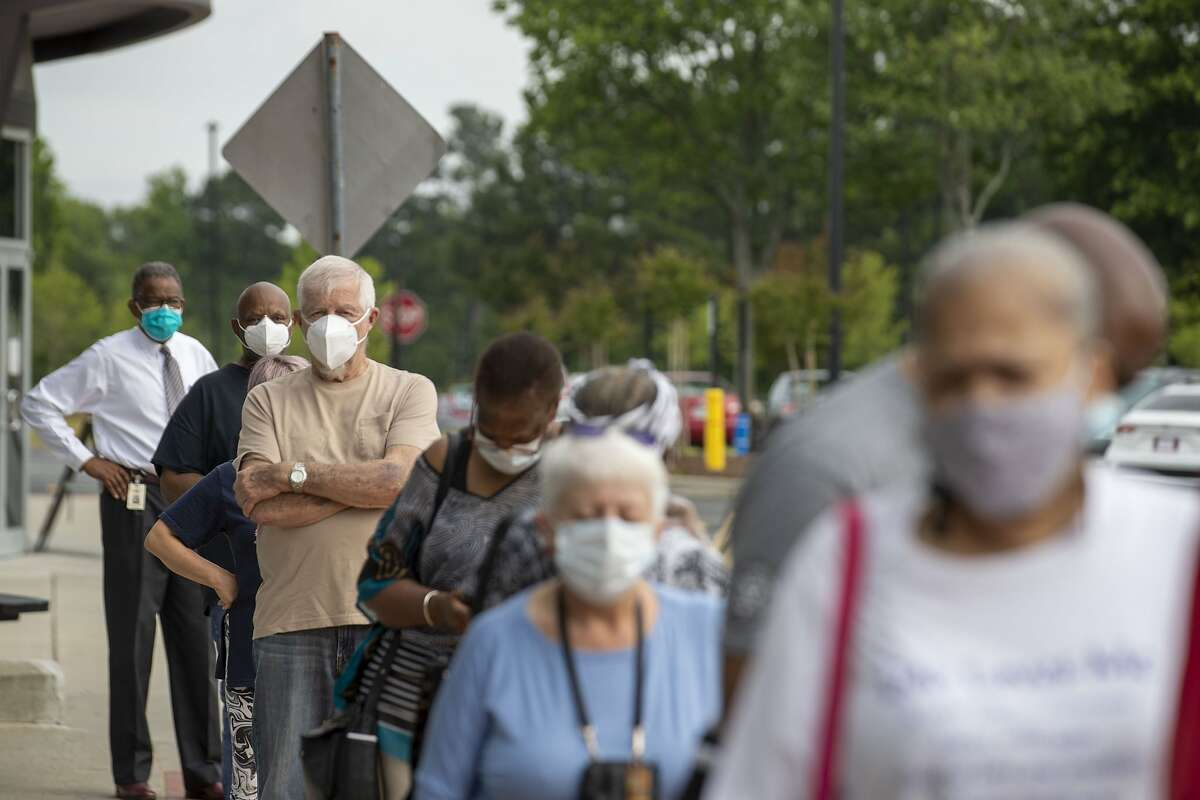 Voters wearing face masks stand in line outside the Gwinnett County Voter Registration and Elections Office to participate in early voting for Georgia's primary election in Lawrenceville, Ga., on May 18.