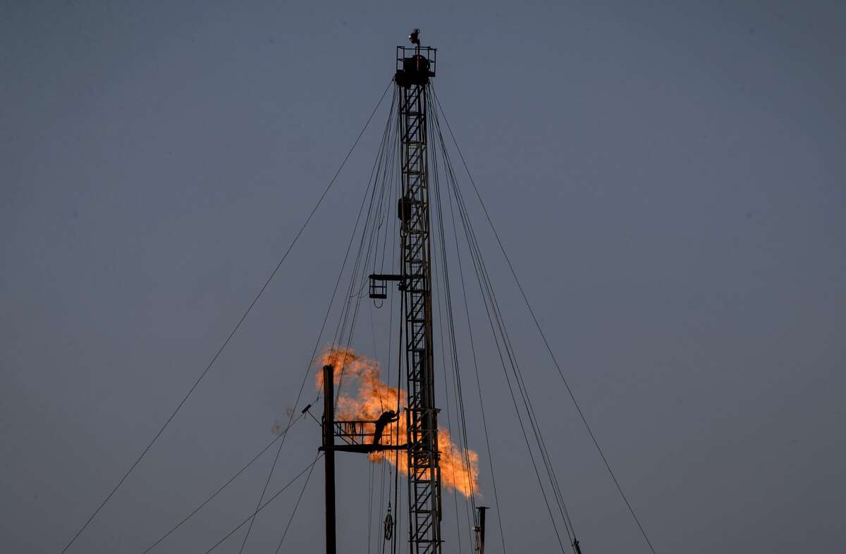 A drilling rig operates as a flare burns in the background in Reeves County on Friday, Dec. 20, 2019, near Pecos.