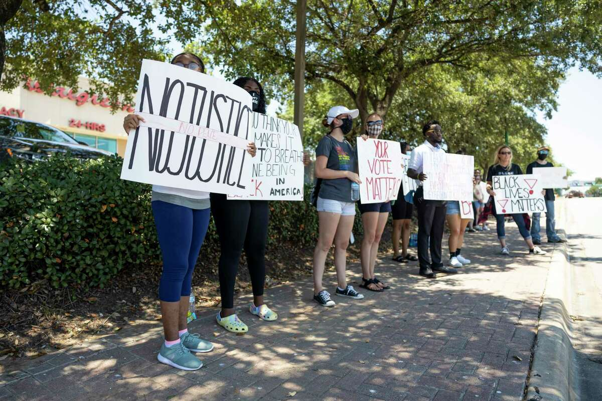 Demonstrators hold signs along the intersections of Davis St. and Thompson St. in Conroe, Sunday, June 14, 2020. An estimated 70 demonstrators participated in the march.