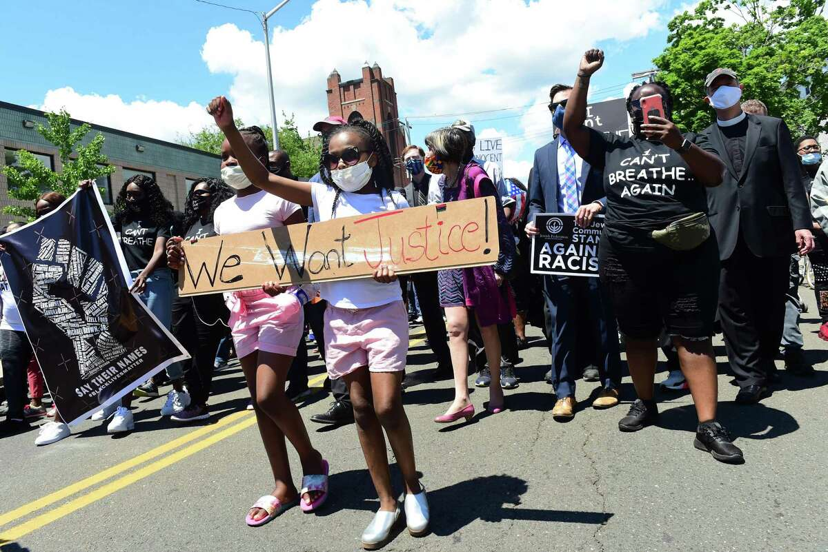 Leah Evans, center left, 10, of Bridgeport and her friend, Halo Daniels, center right, 9, of New Haven participate in the Prayer, Protest & Peace March starting from Varick Memorial AME Zion Church to the New Haven Green on Sunday. Below,