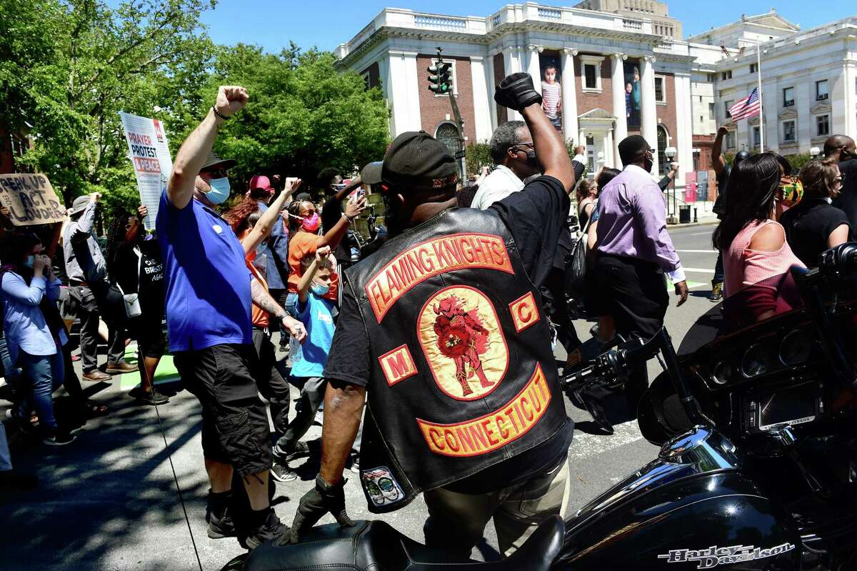 Rodney Williams, center, of the Flaming Knights Motorcycle Club watches protesters in the Prayer, Protest & Peace March enter the New Haven Green on June 14, 2020.