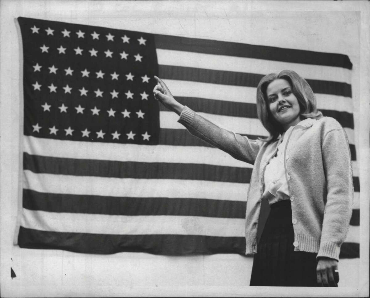 New York - Miss Sandra Norris of Westmere points to the 46 stars on an old American Flag displayed this week at Albany Savings Bank. The flag, official from 1908 to 1912, was borrowed by the Lewis W. Oppenheim Veterans of Foreign Wars Post 1019 from a VFW post in Depew for the display in observance of Flag Day Sunday. The Albany post asks residents to search their homes for other old flags for display on future Flag Days. Miss Norris, 22, is a clerk in the bank's mortgage department. Undated (Knickerbocker News Staff Photo/Times Union Archive)