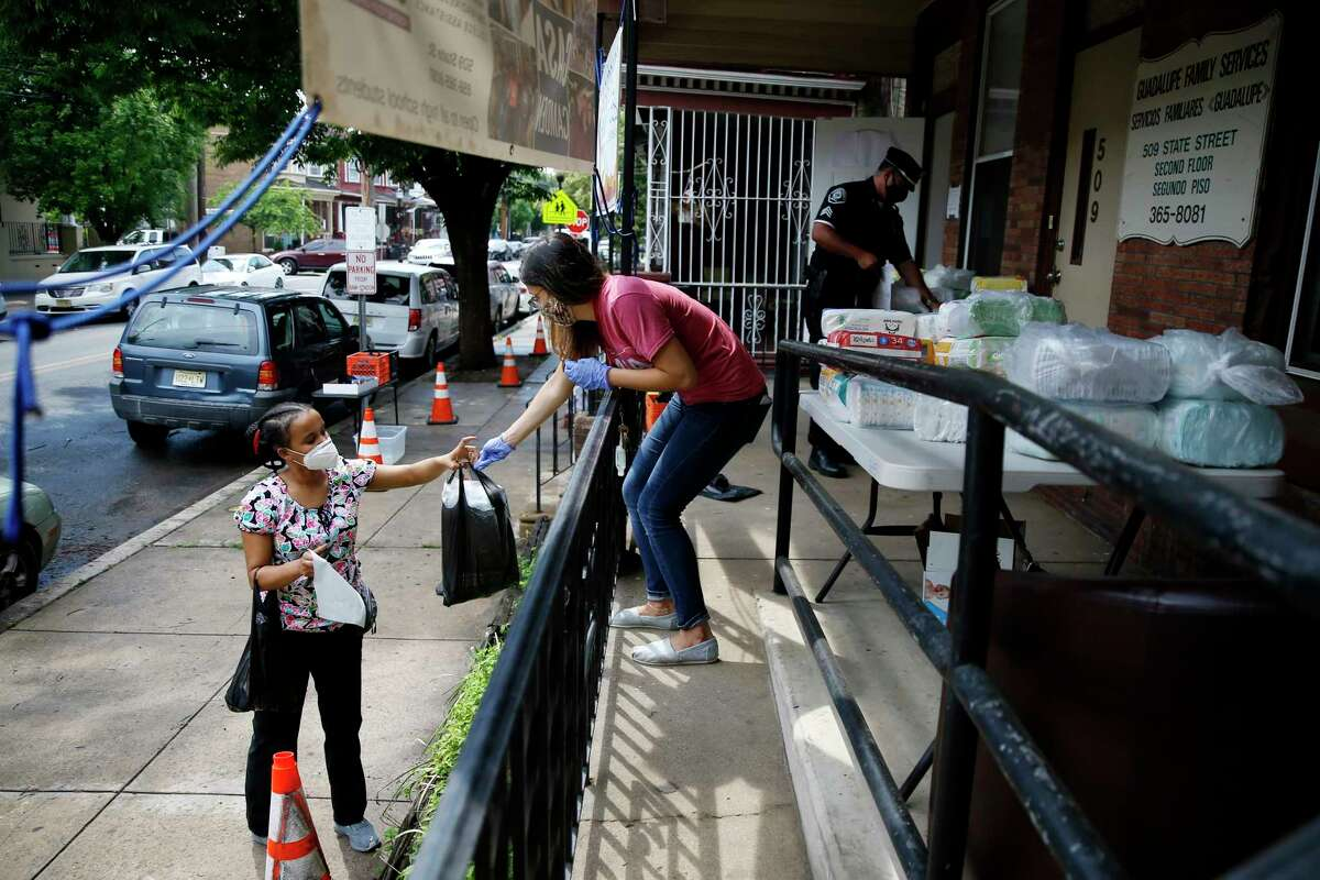 In this June 11, 2020, photo Lourdes Sherby, center, with Guadalupe Family Services, hands diapers to Louisa Peralta in Camden, N.J. a€œI think wea€™re received a lot better than we used to be,a€ said Sgt. Dekel Levy, 41, as he helped hand out diapers to a steady stream of young mothers Thursday afternoon at Guadalupe Family Service. (AP Photo/Matt Slocum)