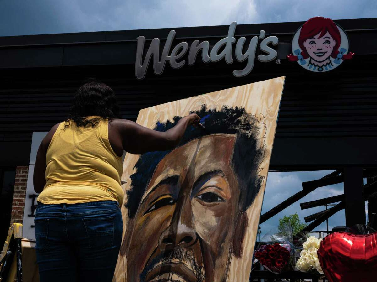 Ashley Dopson paints a portrait of Rayshard Brooks outside of the Wendy's restaurant where Brooks was shot and killed by police in the parking lot, in Atlanta, June 14, 2020. Brooks had fallen asleep in his vehicle and was shot after grabbing a Taser from an officer, the authorities said, prompting fresh unrest in the city. (Joshua Rashaad McFadden/The New York Times)