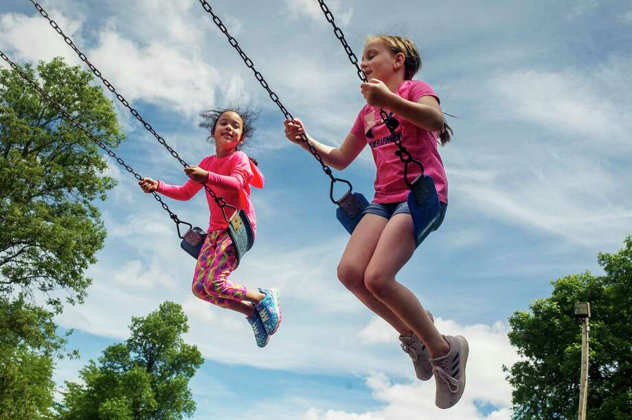 Let's play! Ava Moore, 6, left, and Adalae Zablocki, 8, right, swing side by side as they play together Saturday afternoon at the Plymouth Park playground. Midland's playgrounds were reopened Tuesday, June 9 after being closed for more than two months due to the coronavirus. (Katy Kildee/kkildee@mdn.net)